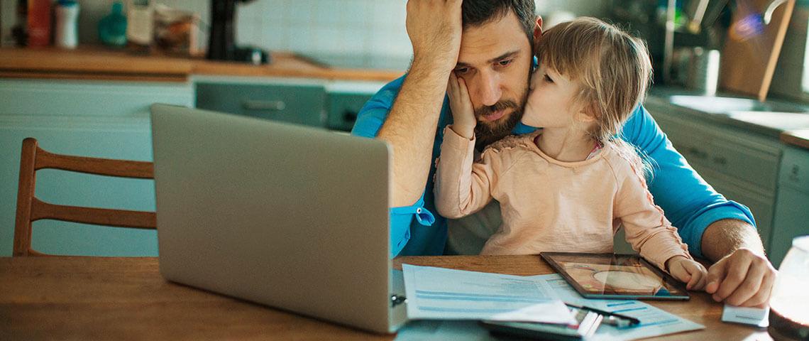 Verzweifelter Vater sitzt mit Tochter vor seinem Laptop