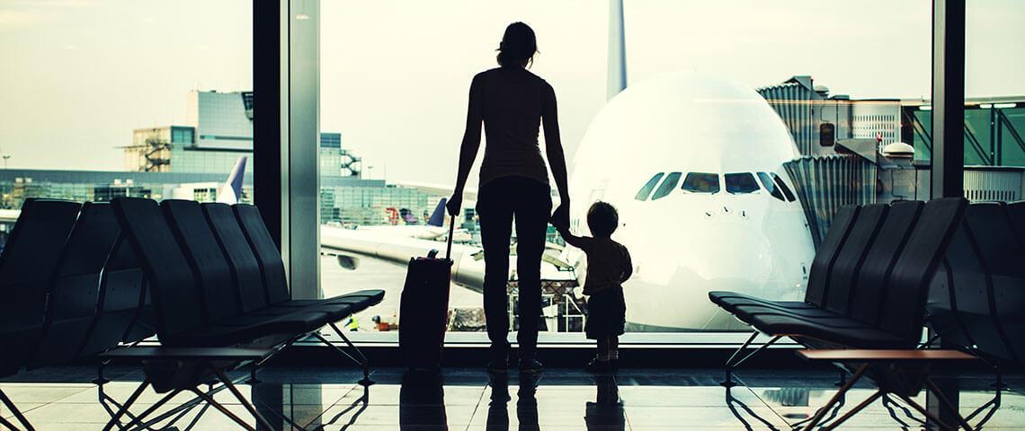Reiserecht - Mutter und Kind am Flughafen-Gate betrachten die Flugzeuge