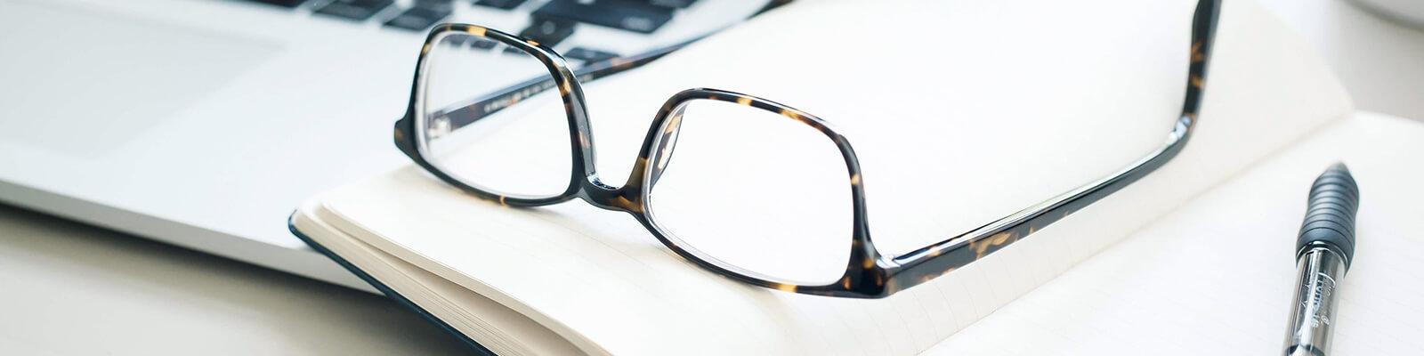 Notebook und Notizbuch mit Brille aufliegend