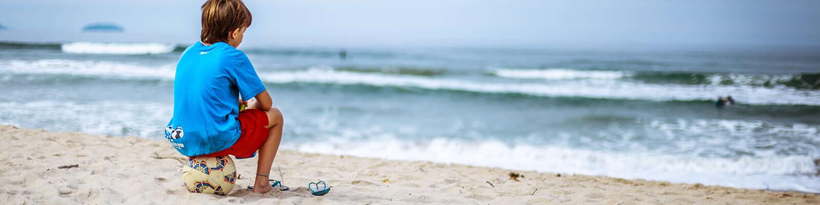 Kleiner Junge sitzt auf Fußball am Strand